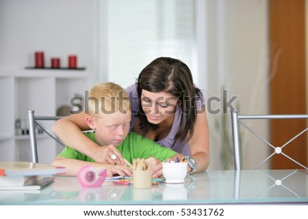 Portrait of a young woman helping a little boy to do homework - stock photo