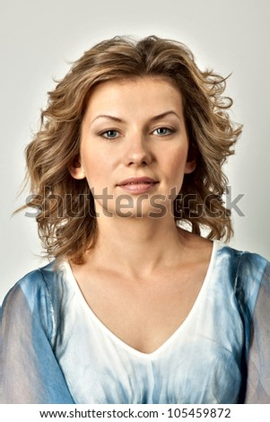 Portrait of a young woman. Her hair is wild and she is wearing a blue dress which is off one shoulder. Vertical shot.