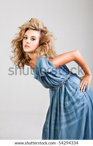 Portrait of a young woman. Her hair is wild and she is wearing a blue dress which is off one shoulder. Vertical shot. Isolated on white.