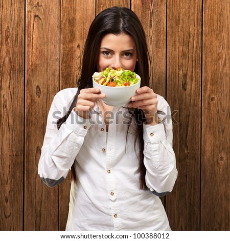 portrait of a young woman holding a fresh salad against a wooden wall