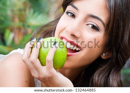 Portrait of a young woman holding a green apple