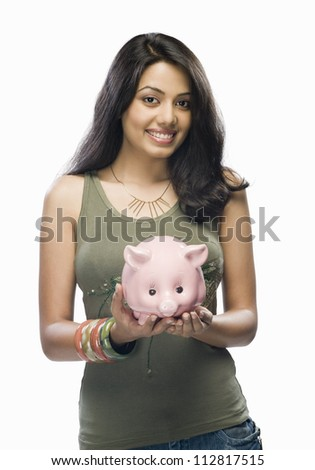 Portrait of a young woman holding a piggy bank