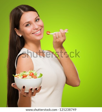 Portrait Of A Young Woman Holding A Salad against a green background