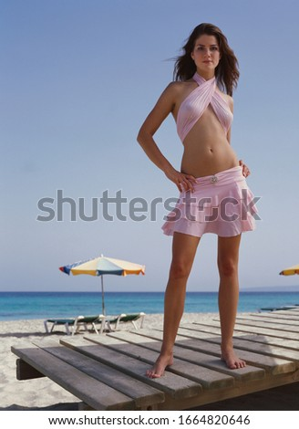 Portrait of a young woman holding a sarong against blue sky