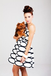 Portrait of a young woman holding a small dog. She is dressed in a black and white dress. Vertical shot.