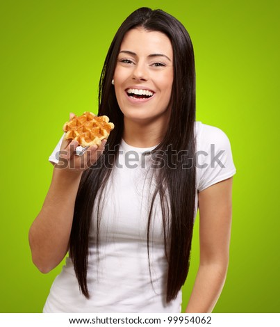 portrait of a young woman holding a waffle over a green background