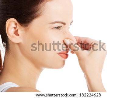 Portrait of a young woman holding her nose because of a bad smell.  #182224628