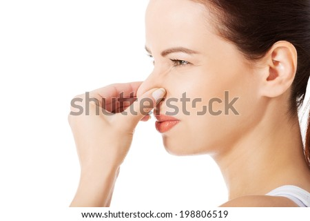 Portrait of a young woman holding her nose because of a bad smell. #198806519