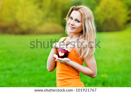 portrait of a young woman holding red apple with heart shape