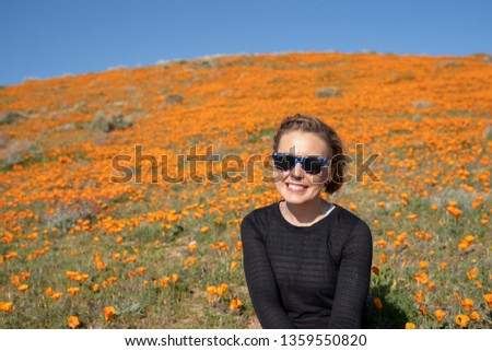 Portrait of a young woman in a black top in the wildflower field of poppies during the California super bloom