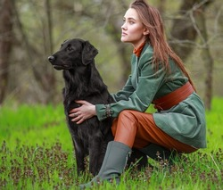 Portrait of a young woman in a country style clothes with black retriever dog in autumn forest