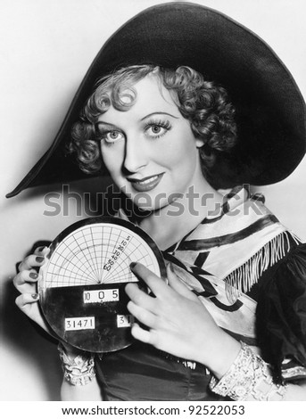 Portrait of a young woman in a hat holding a newly invented speedometer