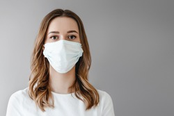 Portrait of a young woman in a medical mask isolated over grey background. Young girl patient stands against the wall background, copy space for text