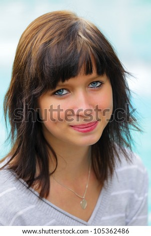 Portrait of a young woman in background blue water, outdoor in city park in a small city \