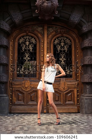 Portrait of a young woman in front of the old decorated door. Outdoors.