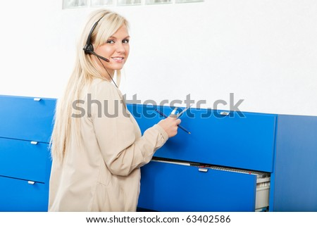 Portrait of a young woman in front of wall drawers with documents
