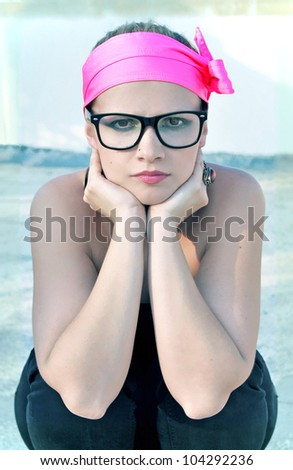 Portrait of a young woman in geek glasses and a pink headband