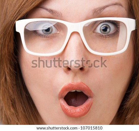 portrait of a young woman in glasses surprised with his mouth open in surprise and delight