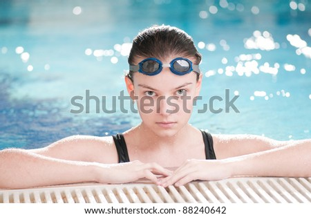 Portrait of a young woman in goggles in swimming pool
