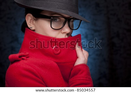 Portrait of a young woman in red trench coat, with glasses, and blue background.Hiding the face.