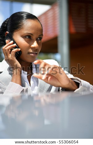 Portrait of a young woman in suit phoning