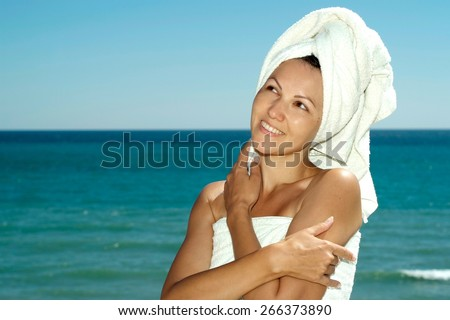 portrait of a young woman in towel on a background of the sea