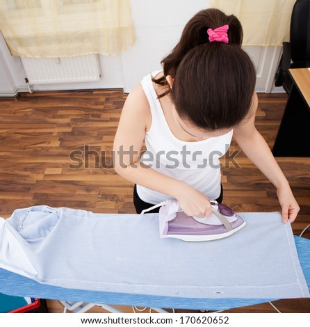 Portrait Of A Young Woman Ironing On Ironing Board