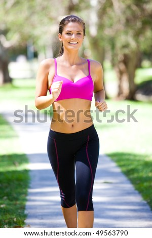 Portrait of a young woman jogging in an outdoor setting. Vertical shot. - stock photo