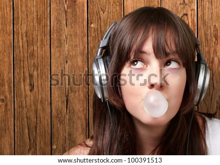 portrait of a young woman listening to music with bubble gum against a wooden wall