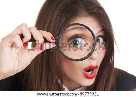 Portrait of a young woman looking at the camera through a magnifying glass with a surprised expression. Focus on the hand.