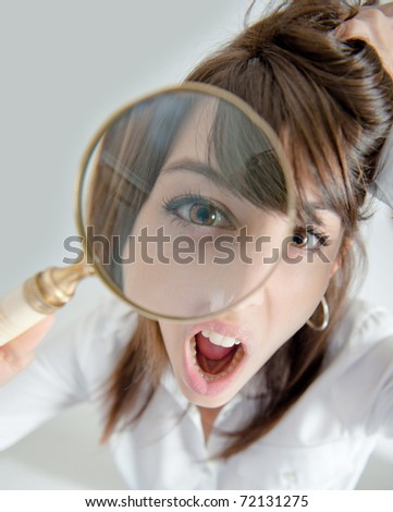 Portrait of a young woman looking at the camera through a magnifying glass with an outraged expression