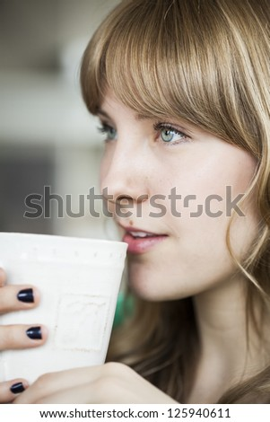 Portrait of a young woman looking away from the camera holding a cup of coffee.