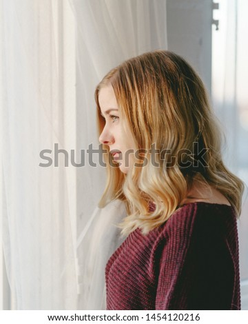 Portrait Of A Young Woman Looking Out A Window