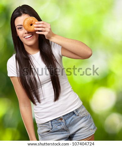 portrait of a young woman looking through a donut against a nature background