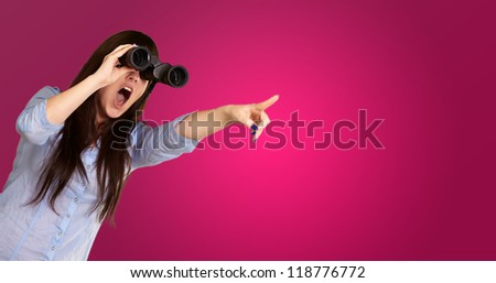 Portrait Of A Young Woman Looking Through Binoculars On Pink Background