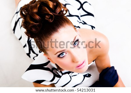 Portrait of a young woman lying. Her hair is styled in an updo and she is wearing a black and white dress, gloves and high heels. Vertical shot. Isolated on white.