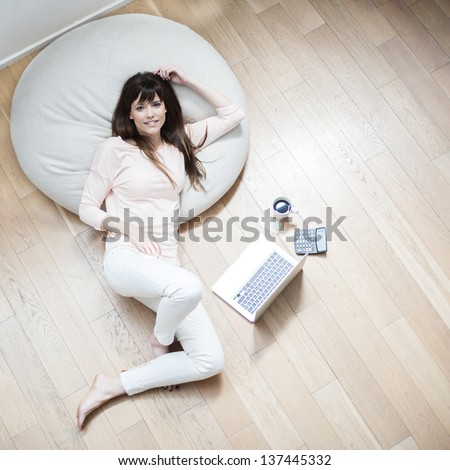 Portrait of a young woman lying on couch with laptop and cup of coffee