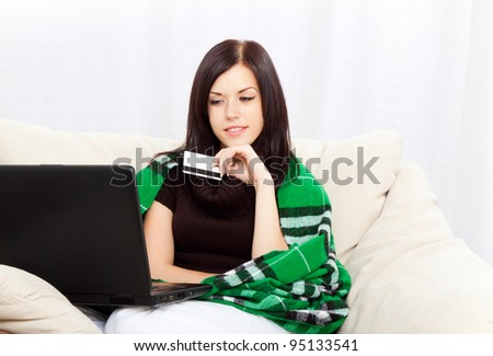 Portrait of a young woman lying on the couch and shopping from the internet using a credit card, sitting on couch at home, living room