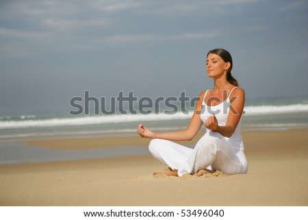 Portrait of a young woman meditating by the sea