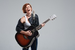 Portrait of a young woman musician with an acoustic guitar. Sing a song on studio microphone on a gray background. She wears black leather jacket and plays rock and roll loudly. Space for text