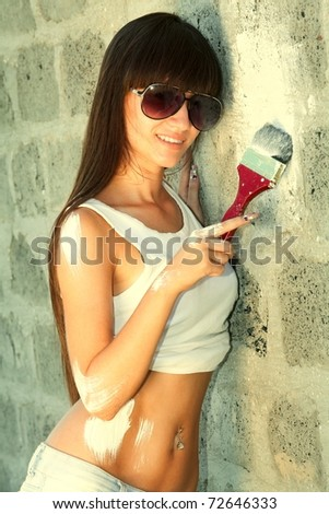 Portrait of a young woman painting the wall with paint-brush