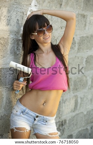 Portrait of a young woman painting the wall with painting roller
