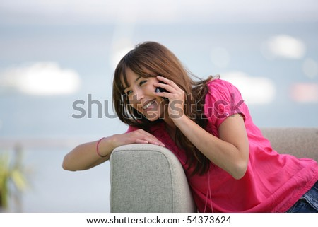 Portrait of a young woman phoning on a sofa