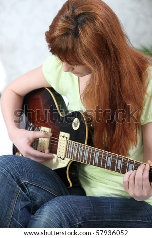 Portrait of a young woman playing the guitar
