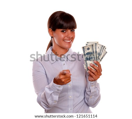 Portrait of a young woman pointing at you and holding dollars on isolated background