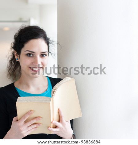Portrait of a young woman reading a book with copy space
