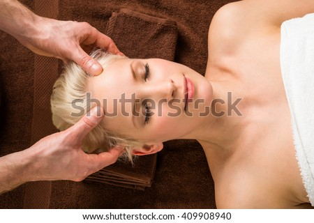 Portrait Of A Young Woman Receiving Head Massage At A Beauty Salon