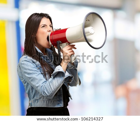 portrait of a young woman screaming with a megaphone indoor