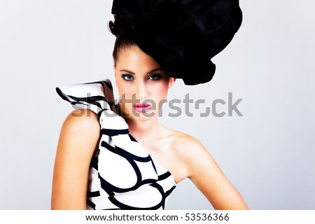 Portrait of a young woman. She is wearing a large hat and a black and white dress with a bow on the shoulder. Horizontal shot.