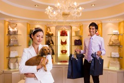 Portrait of a young woman shopping with a dog in a glamorous designer handbag boutique with a male shop assistant is carrying bags in the background.